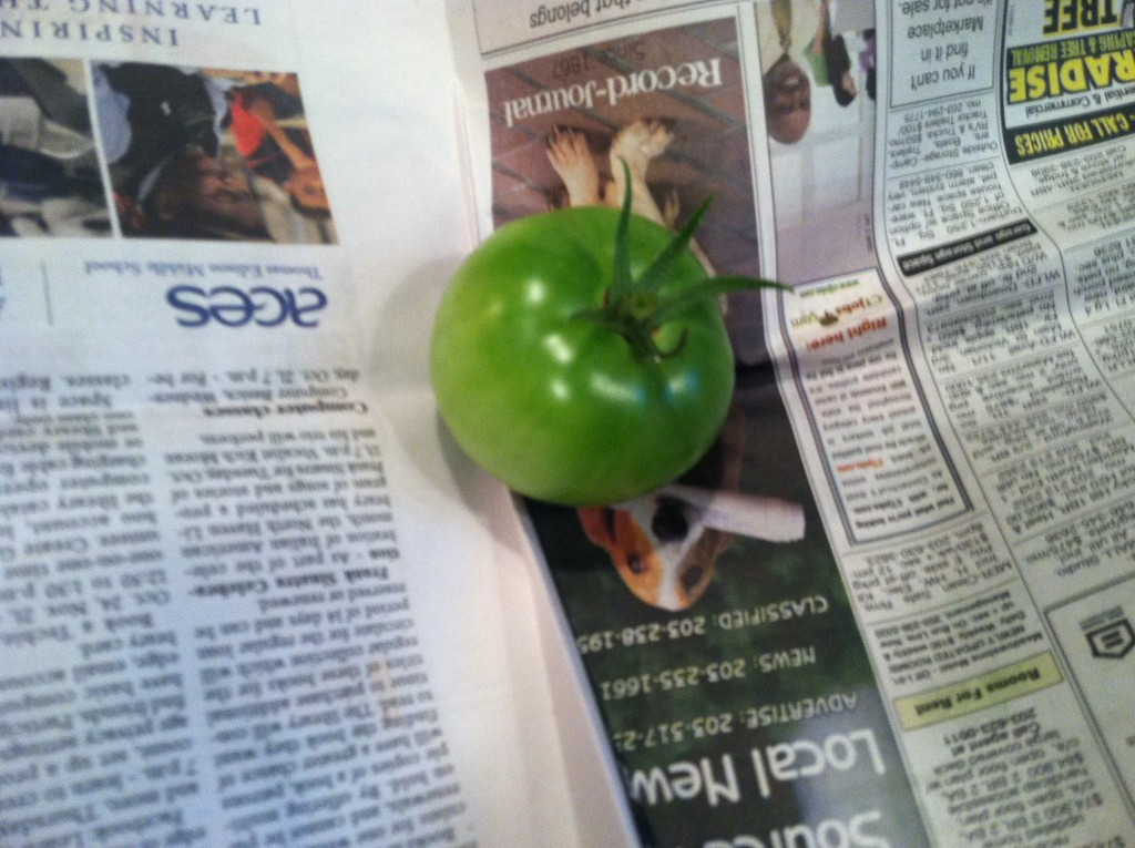 Green tomato wrapped in newspaper